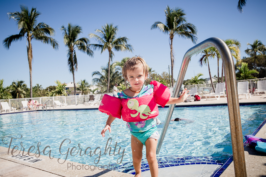 toddler in pool with palm trees and pink float