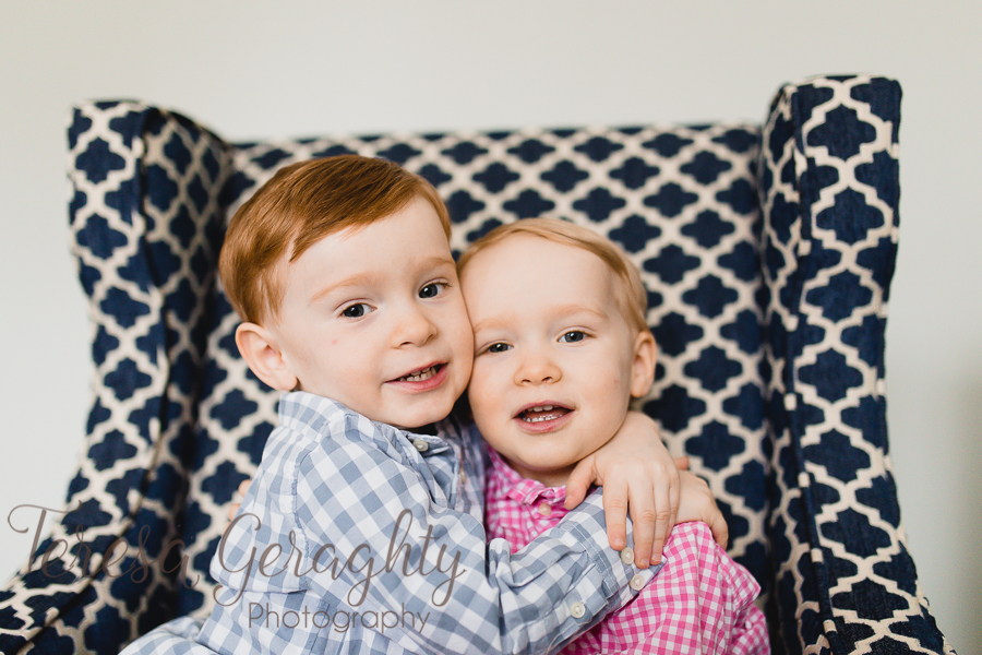 brothers hugging on navy blue couch