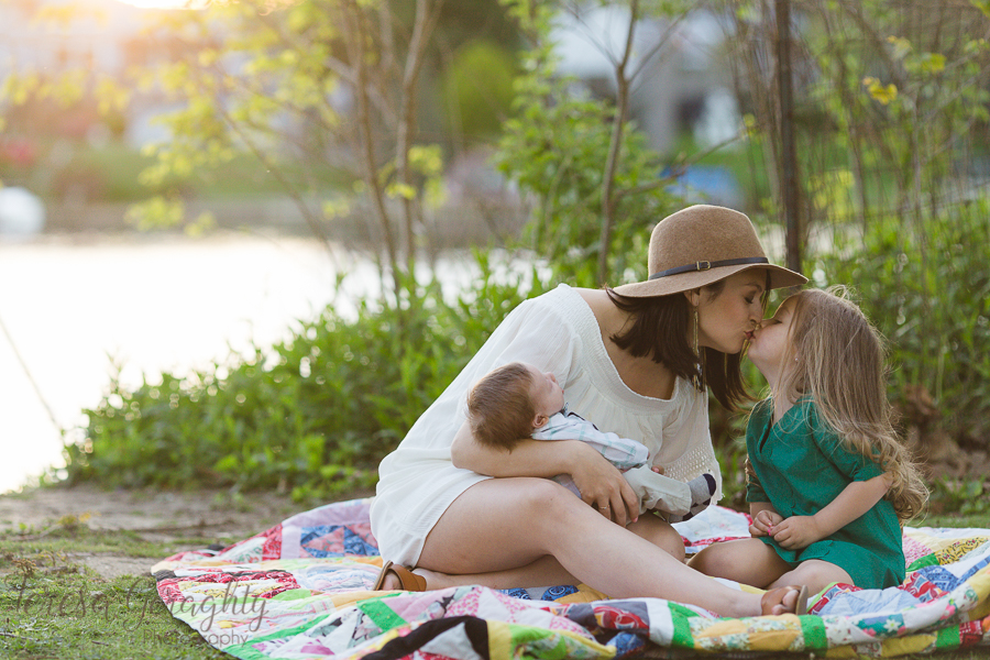 mom kissing toddler daughter on quilt by lake