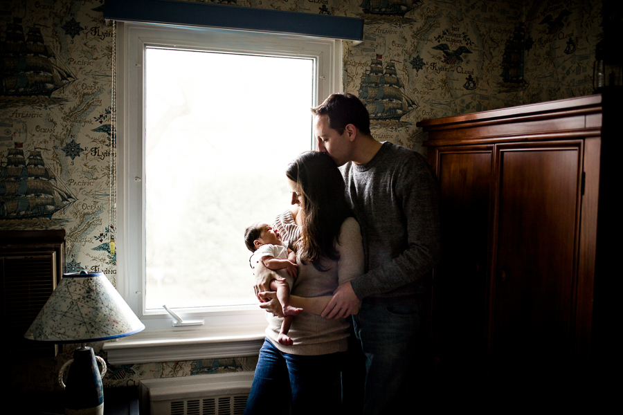 parents in nursery holding baby by window