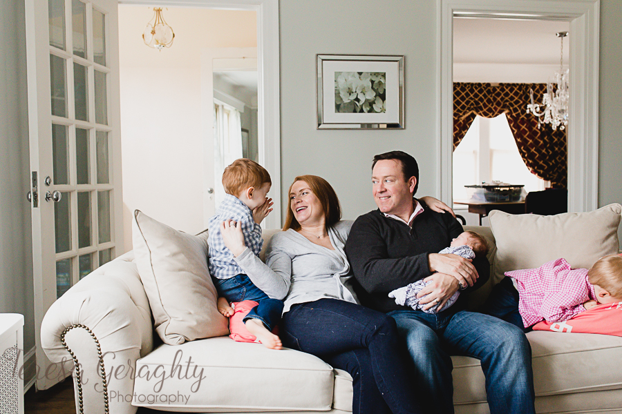 family laughing on white hobnail couch with newborn