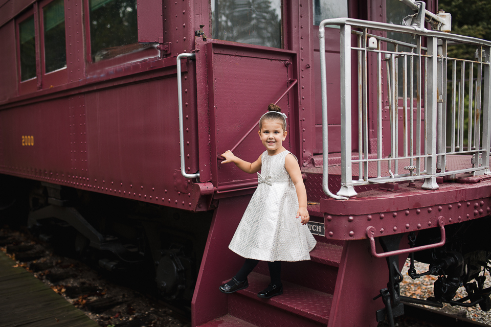 Little girl in Christams dress on vintage red train for holiday photos