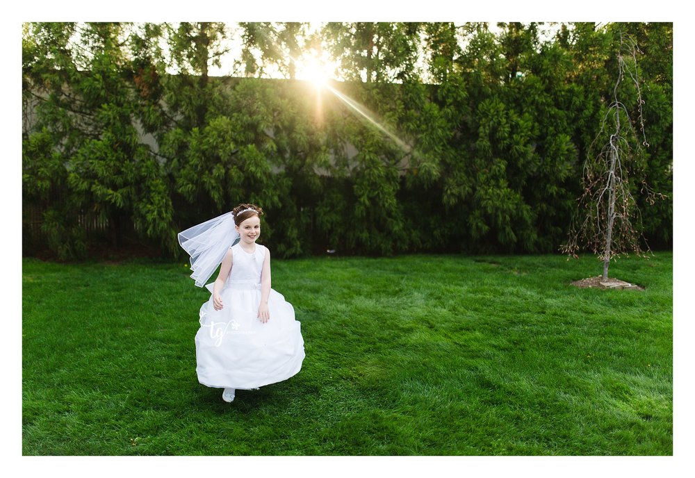 girl in communion dress running on grass with sunset behind her