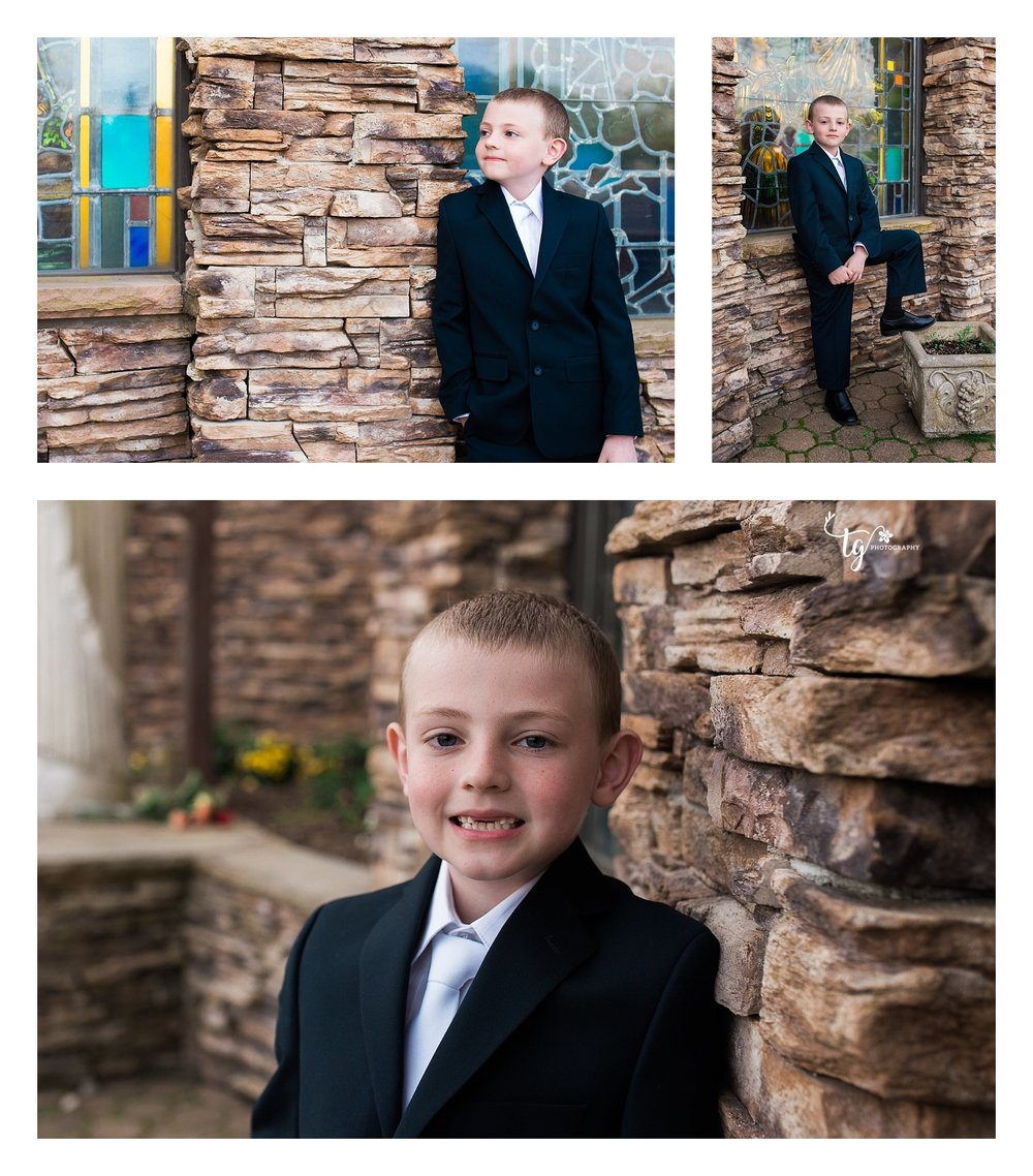 Boy in communion suit leaning against a stone wall