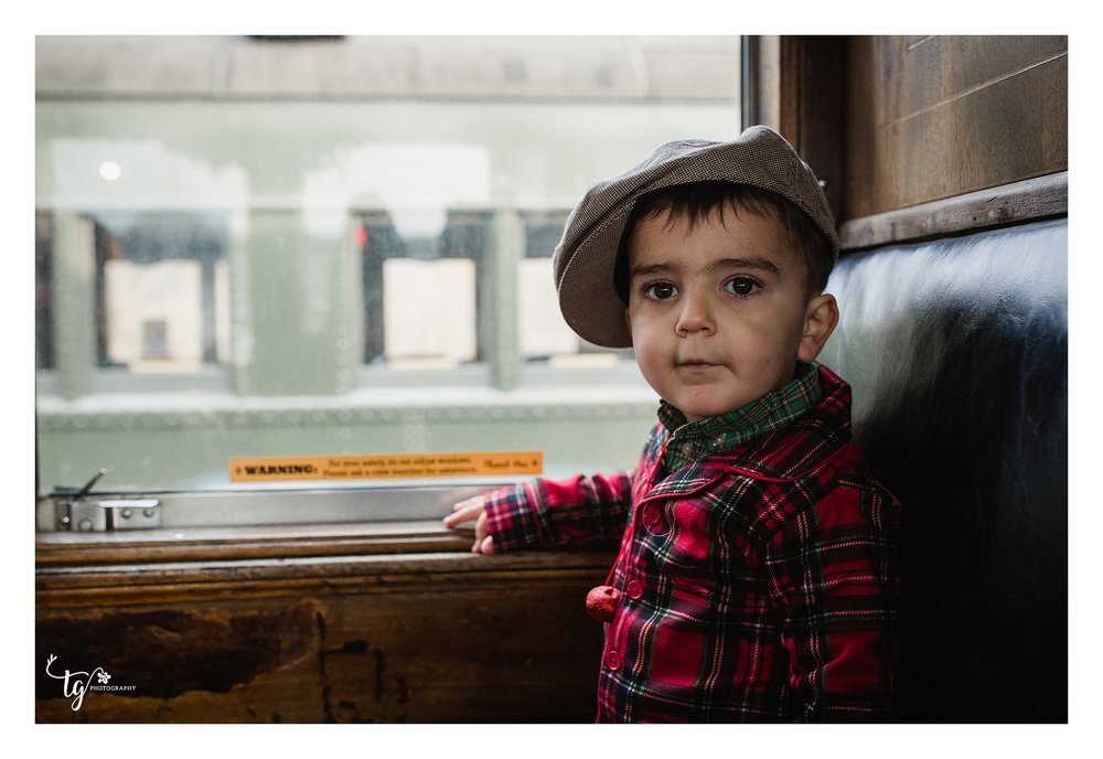 little boy with driver's cap on train
