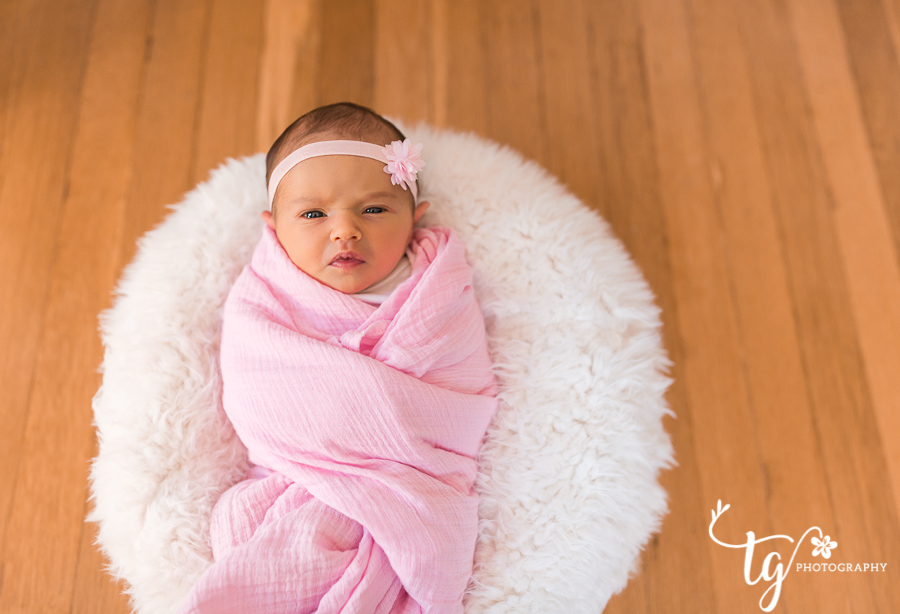 newborn swaddled in pink with eyes open on white pouf