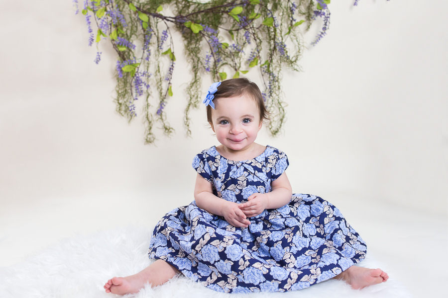 one year old in front of floral vine backdrop