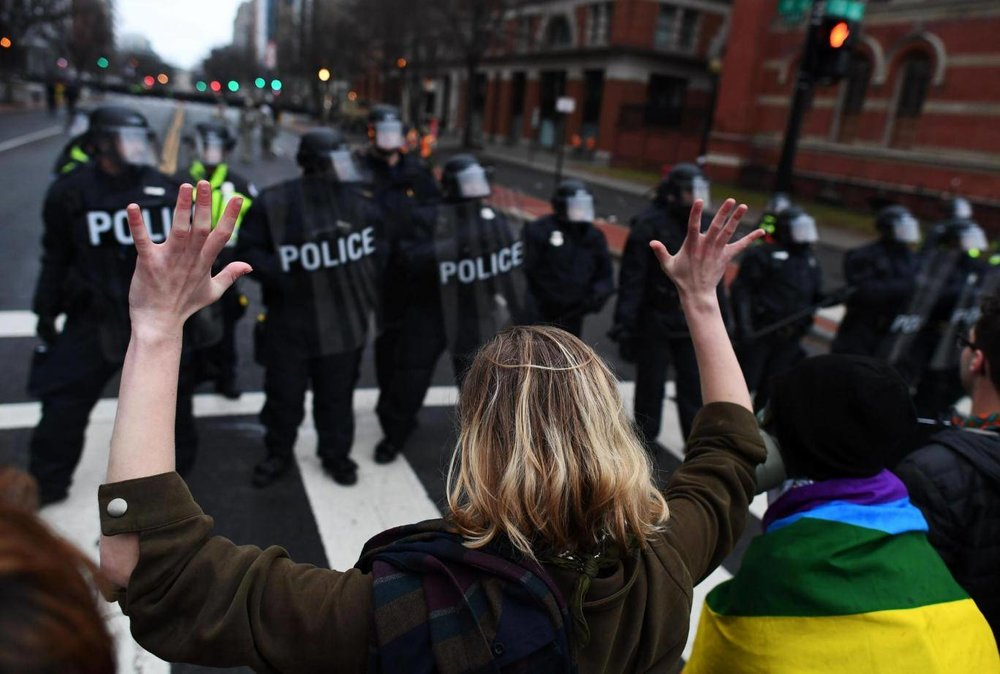 A protester shows the police her peaceful intentions by raising her hands. (Jewel Samad/AFP/Getty Images)