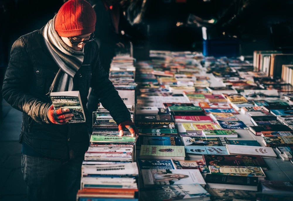 Photo: A man in a hat and scarf holding a book in one hand while browsing for other books on a table.