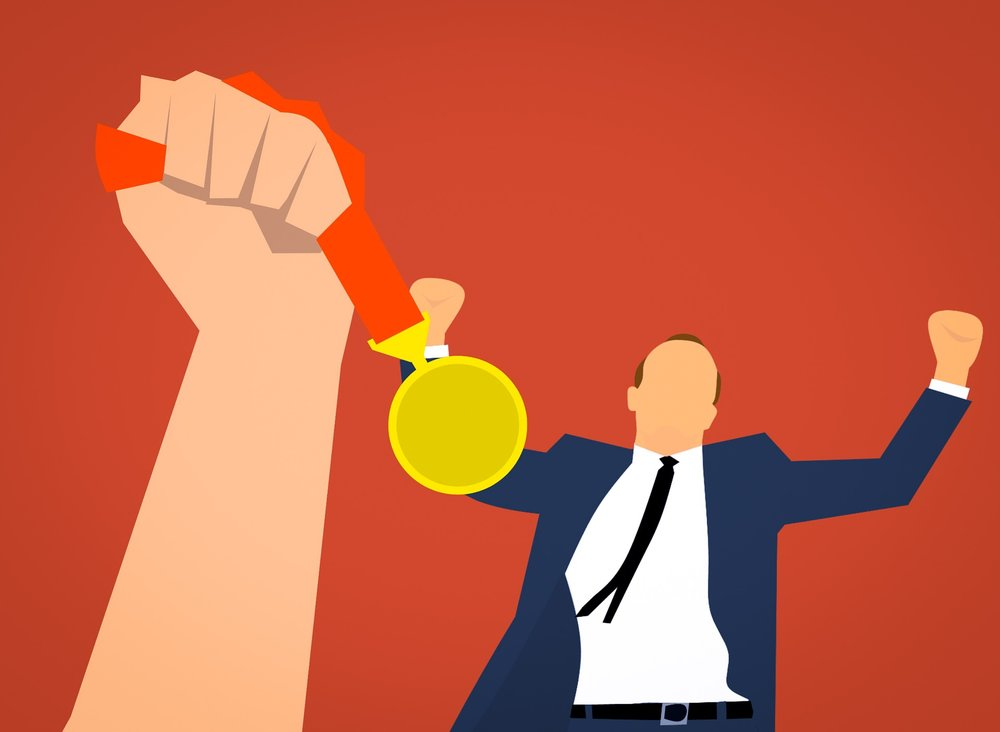 [Artist rendering of a man with his arms in the air as if celebrating. A large hand is in the air in front of him holding out a bright yellow medal.]