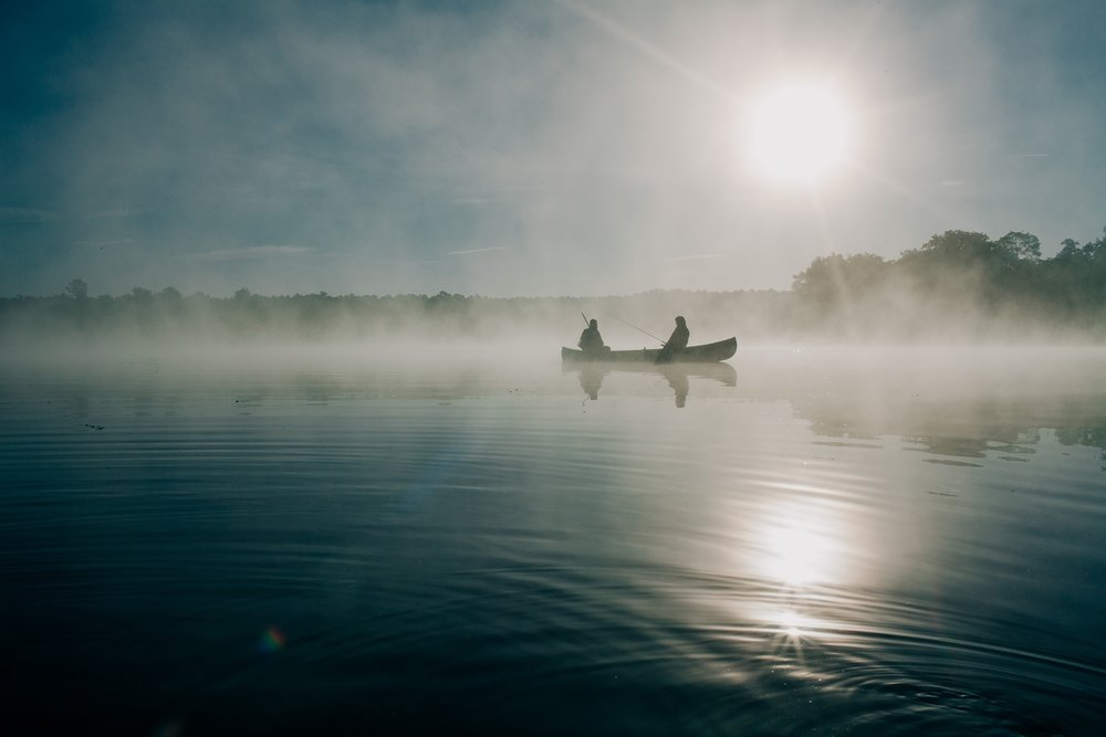 [Two silhouettes of men in the distance in a small canoe, on a foggy lake fishing on a early somber morning.]