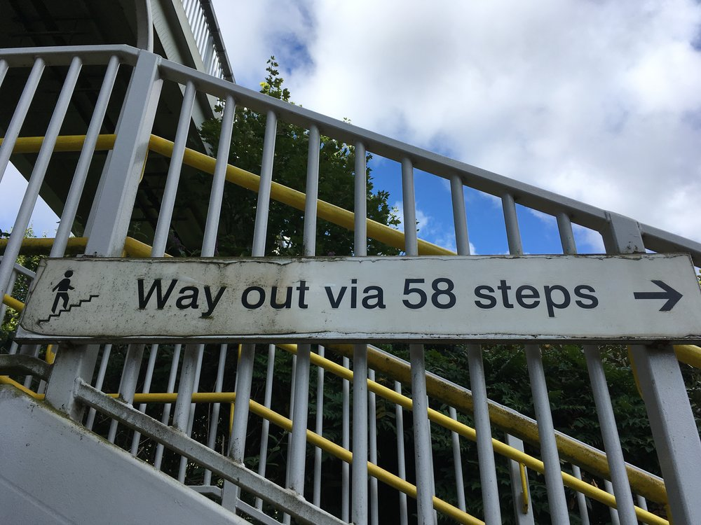 Sign at rail station that says 'Way out via 58 steps'