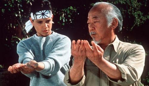 Mr Miyagi en train d'apprendre à bien tenir un livre à don disciple.