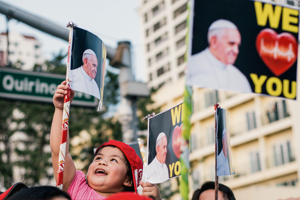 A child waits for the arrival of the Papal Mobile along Quirino Avenue.