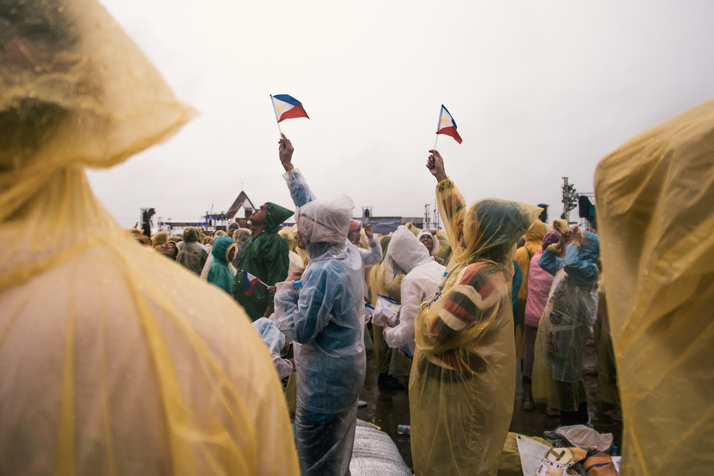 Devotees raise their Philippine flags while they wait for the papal plane to pass by Tacloban skies.
