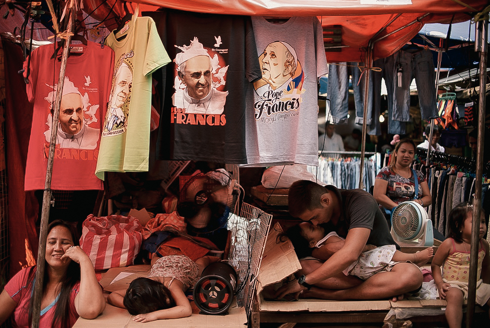 A family takes shelter on a tent which displays t-shirts marked with the Pope Francis' face in Quiapo Market, Manila. Several Pope Francis merchandise were sold in public spaces months before the Papal Visit.