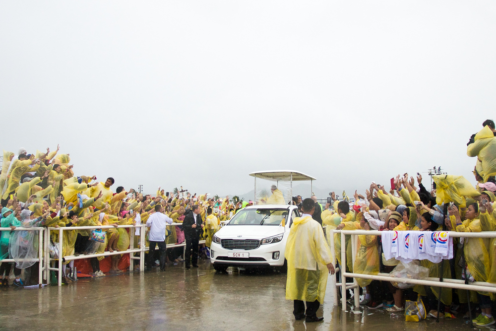 Filipinos reach for Pope Francis as his motorcade passes by them after the mass held in Tacloban. Pope Francis wore similar ponchos with the thousands of Filipinos who stood under the rain.