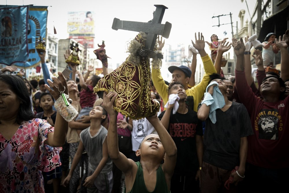 A boy carries a small statue of a dark-skinned Jesus Christ, more commonly known in the Philippines as the Black Nazarene, during the parade of Black Nazarene replicas in Quiapo, Manila January 7, 2016. The parade was done two days before the feast of the Black Nazarene where millions of Filipino Catholics flock in Manila to join the procession and attempt to touch the life-size image of Jesus Christ.