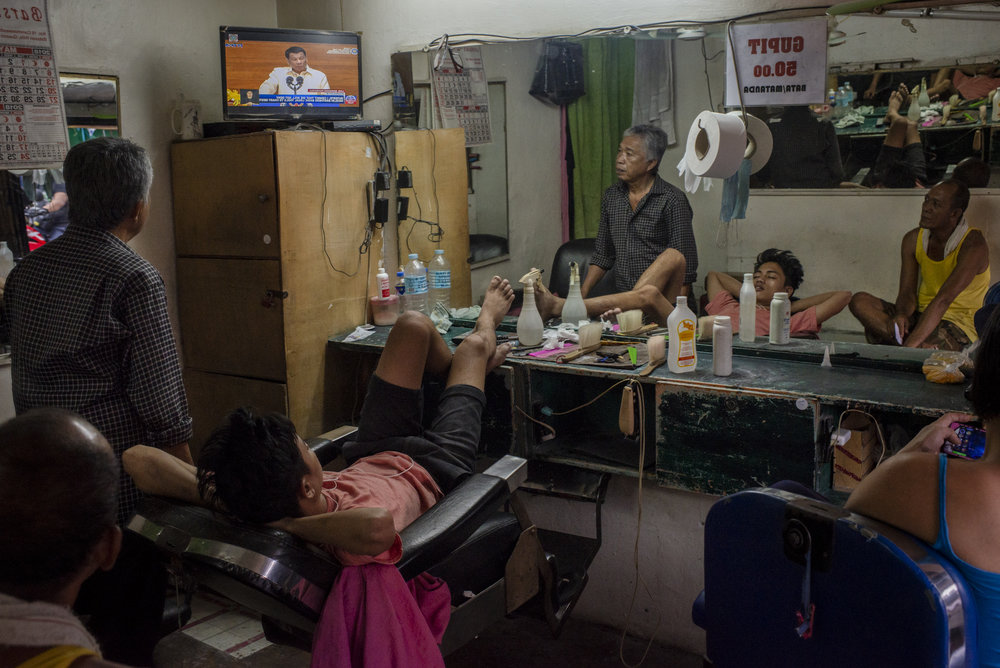 Barbers watch as Philippine President Rodrigo Duterte delivers his second State of the Nation Address, in Quezon City, Metro Manila, Philippines, July 23, 2018.