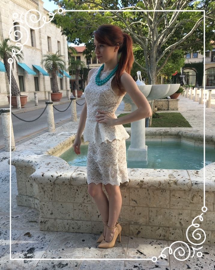 Jessie is rocking a high pony and wearing a white lace peplum dress by Guess, a chunky blue double-strand necklace, and pointy toed nude pumps.