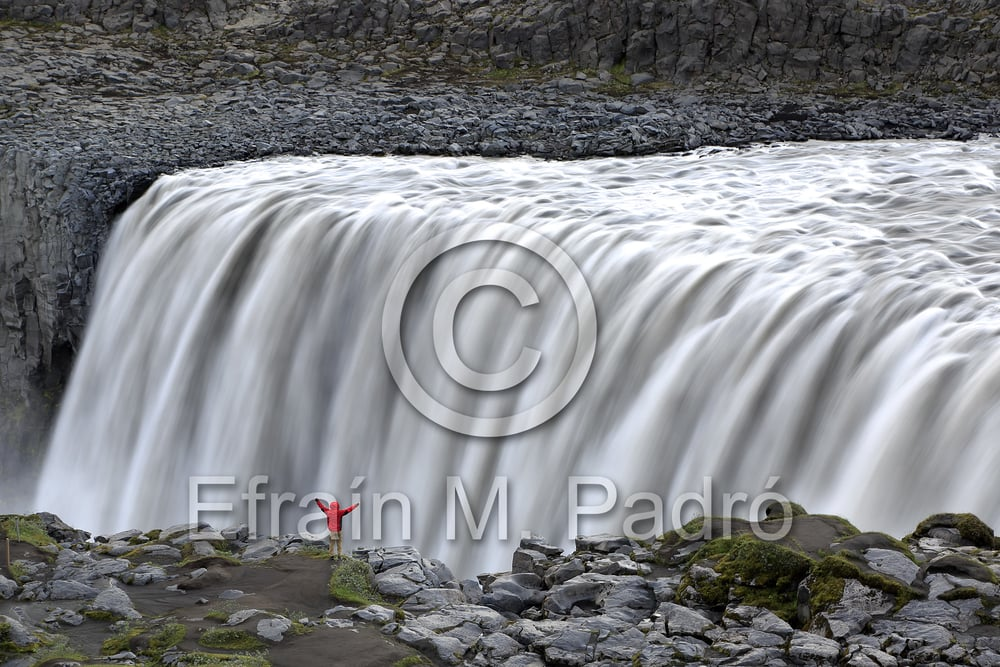 Hiker on rim of Dettifoss Waterfalls, near Reykjahlid, Iceland