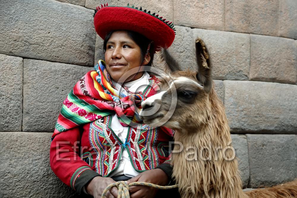 Quechua woman (Viviana), llama and Inca walls, Cusco, Peru