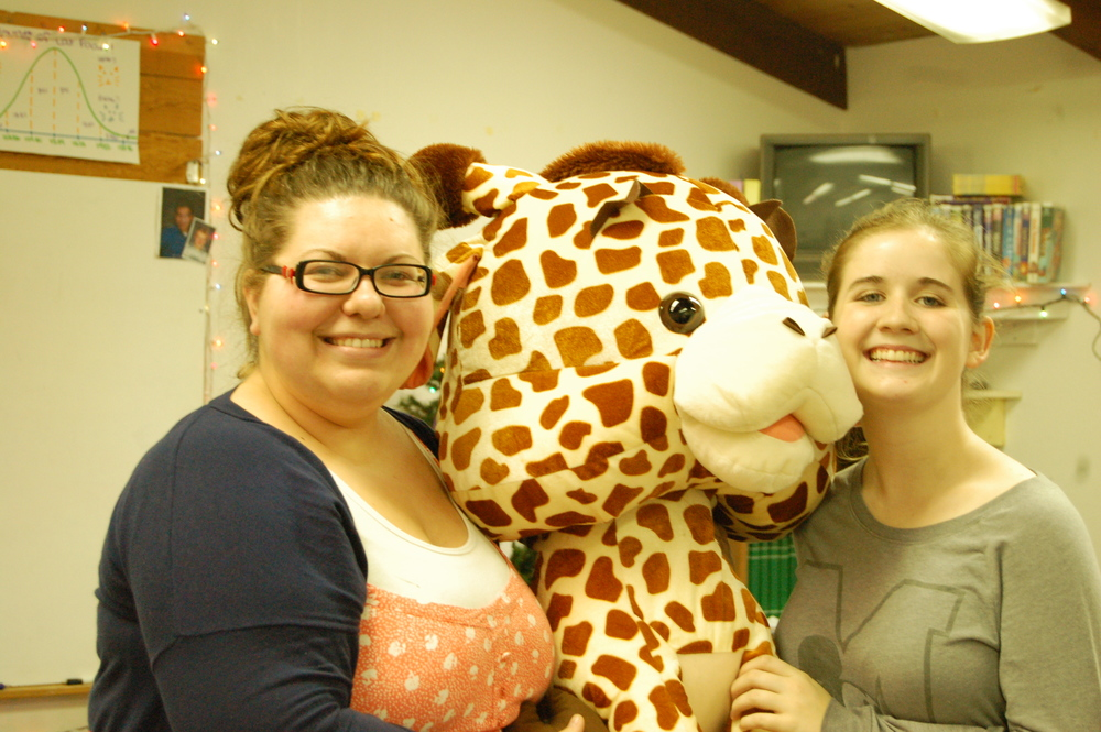 Math teacher Ms. Aswege, senior Katie Costley, and Gerry the Giraffe