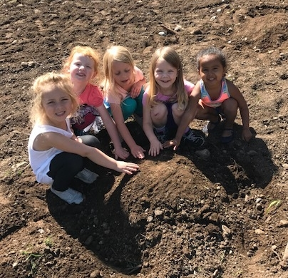 Preschool students are the first to plant pumpkins for this fall's pumpkin patch!