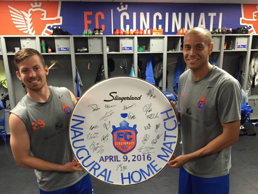 Antoine Hoppenot and Luke Spencer holding up the inaugural drum head after the entire team signed it.