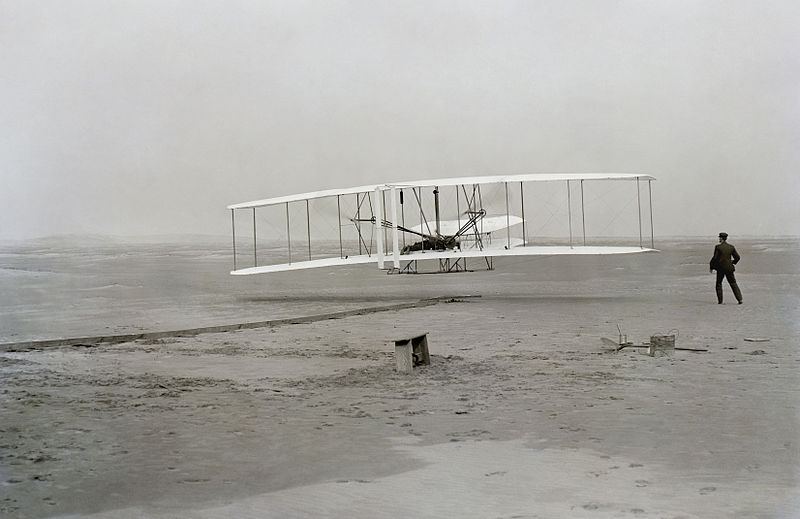 The first flight of the Wright Flyer in 1903. Orville is the pilot and Wilbur stands at the wingtip.  (Library of Congress photo)