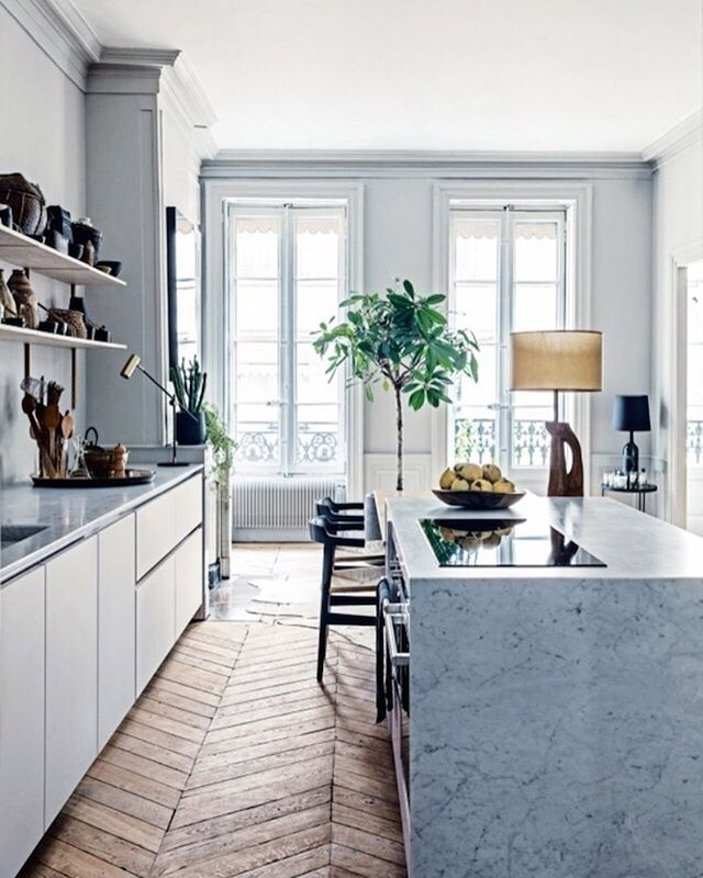 A sleek and modern kitchen in a 19th-century French shell. We particularly love the waterfall island and killer chevron floors! 🇫🇷 || photo by Felix Forest for @vogueliving
