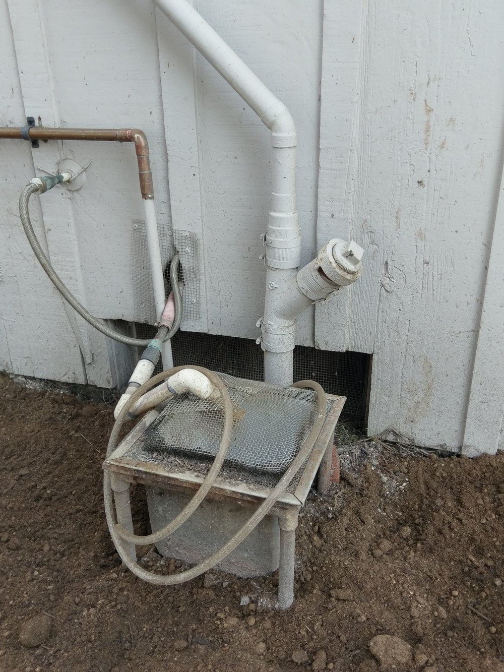 """The dishwasher drain pipe came out of the kitchen through the wall, and then back in. It was connected directly to the sewer line, eliminating the need for a large """"sink"""" (rectangular box), dubbed the """"Chum Bucket by the Garden Chairs."""