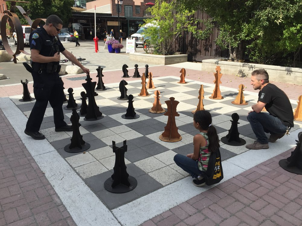 The very first chess game played between officer Jon MonPere and Roundhouse board member Morgan Goodwin, with help from a local 5th grader.