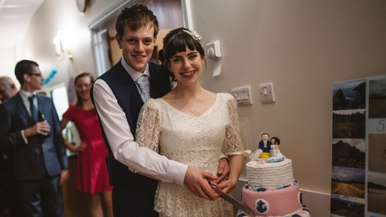 The very gorgeous Rosie and Chris with their beautiful wedding cake and seaside-themed cake topper. Image courtesy of Danni Maytree at  maytreephotography.co.uk