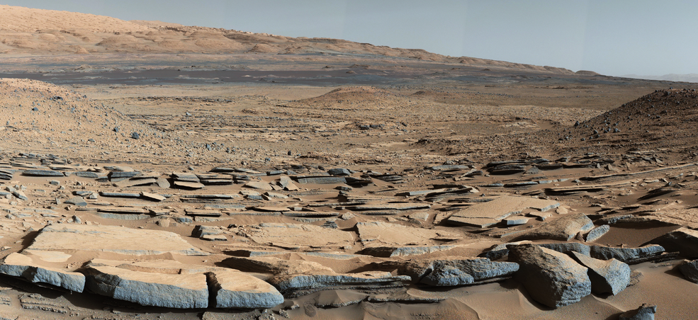 "A view from the ""Kimberley"" formation on Mars taken by NASA's Curiosity rover. The strata in the foreground dip towards the base of Mount Sharp, indicating flow of water toward a basin that existed before the larger bulk of the mountain formed.   Credits: NASA/JPL-Caltech/MSSS"