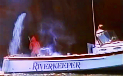 1983 video capture of John Cronin bringing the 25-foot Hudson Riverkeeper vessel alongside the hull of a 750-foot Exxon oil tanker to sample its ballast discharge, with crew mate Andra Sramek (in orange foul weather gear).