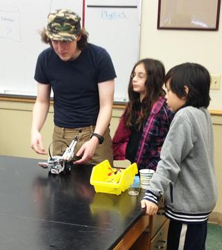 J.D. Cronin, a student of Chad Cianfrani at Oakwood Friends School, instructs Arlington Middle School students in robotics and sensors.