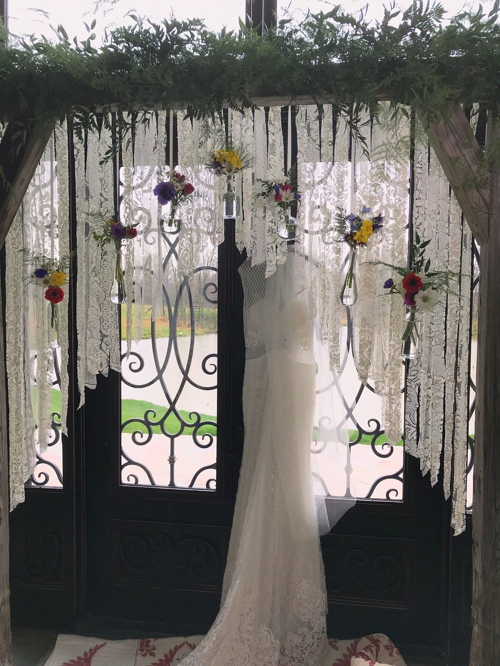 Meagan's arbor—lace strips and hanging bottles with tiny bouquets