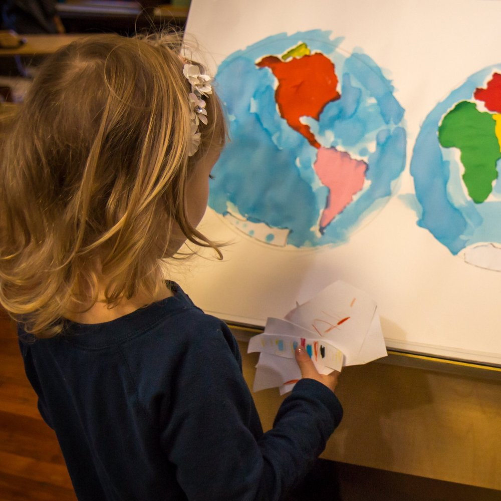 Preparing to label continents on her watercolor map of the two hemispheres of the Earth