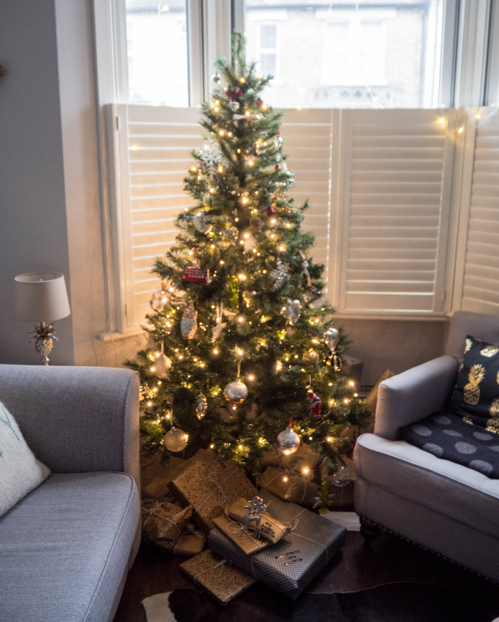 Christmas tree in a small lounge with shutters.