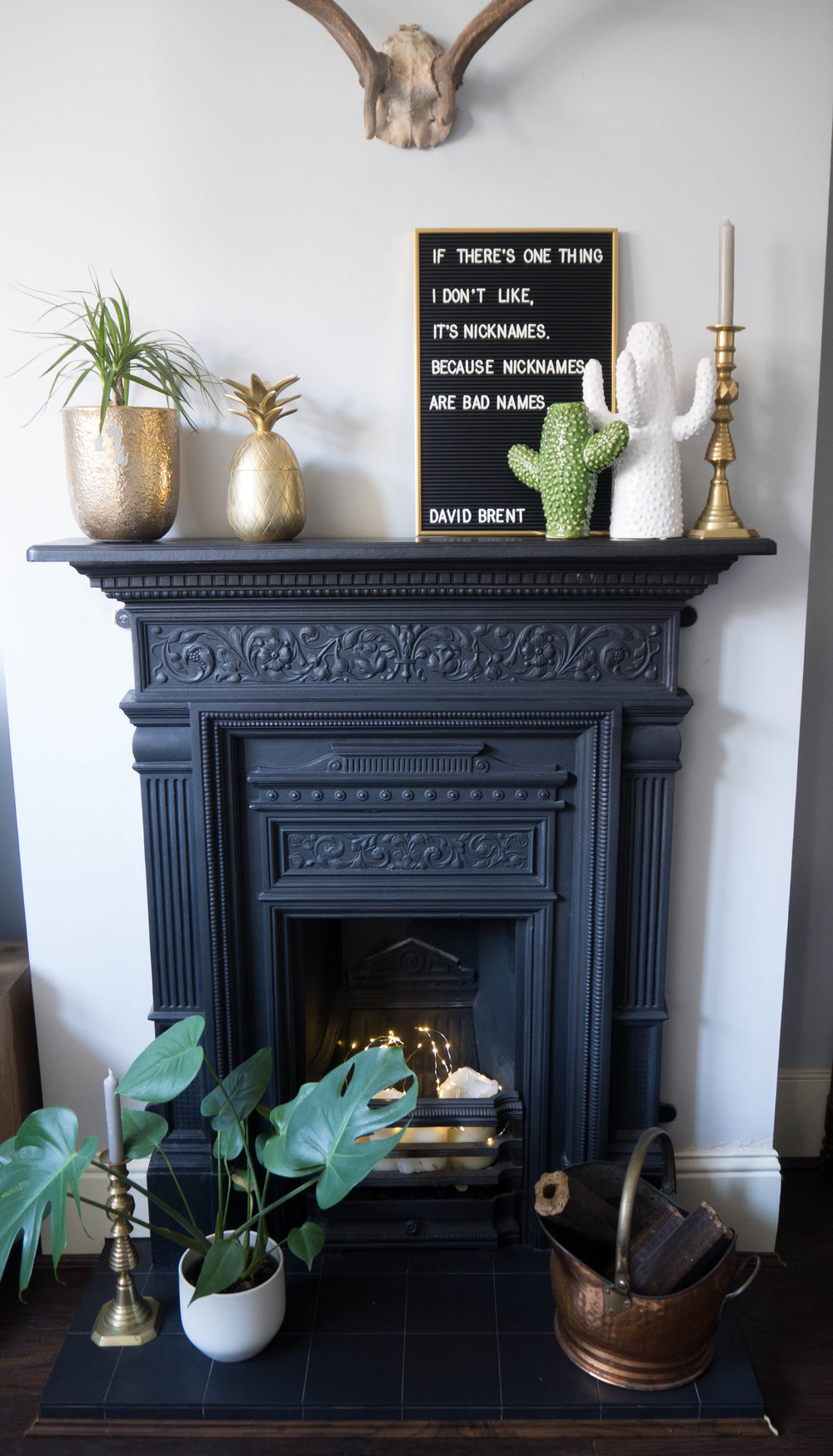 My fireplace mantle with mesage board, brass pineapple and ceramic cactus vases.