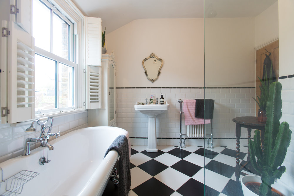 Black and white tiled, Victorian style bathroom with roll top bath.