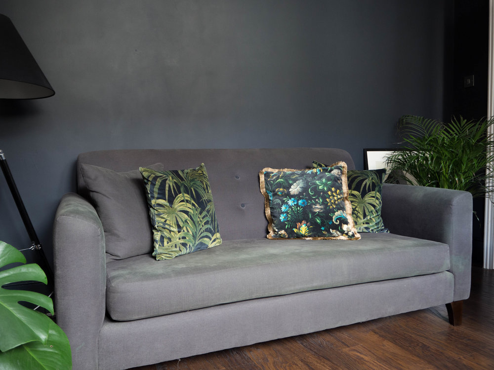dark lounge with palm printed cushions