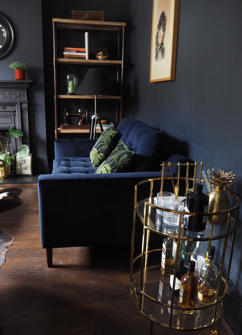 Style it dark! Railings walls, brass bar cart and House of Hackney palmeral  printed cushions on a navy velvet sofa