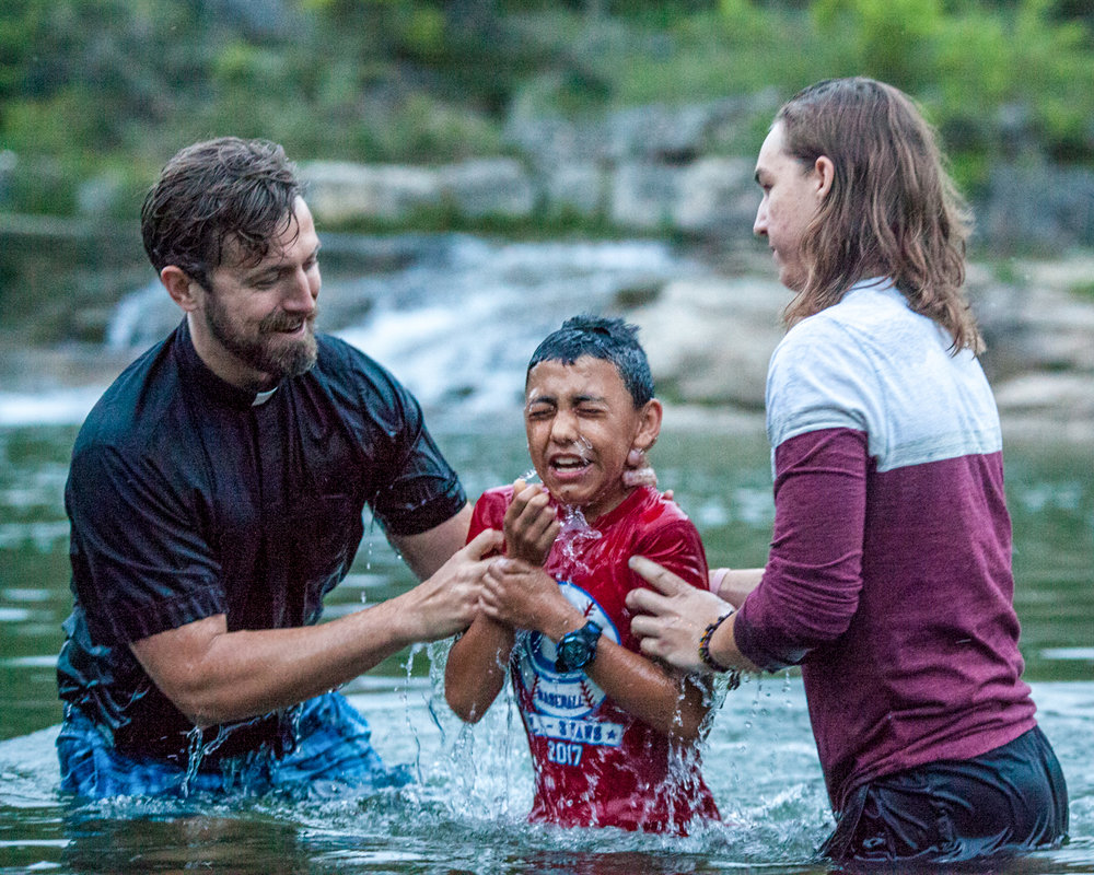 """Reverend Kurt Hein, with help from friend Daniel Guenat, baptizes Christopher Cano, 10, on Easter Sunday. He was baptized alongside three of his siblings and said the baptism was """"cold but fun."""" The Light of Christ Anglican Church held a sunrise service in Blue Hole Park."""