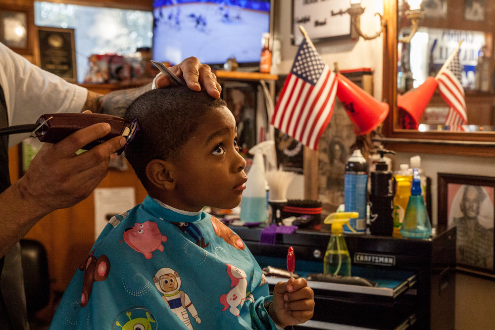Devan Harris Jr., 4, tries to sit still during a haircut from Nikolas Shanklin at Papa Frank's Barber Shop. Proprietor Mr. Shanklin named his business after his grandfather, Frank Miller, a patriarch of the black community in Georgetown.