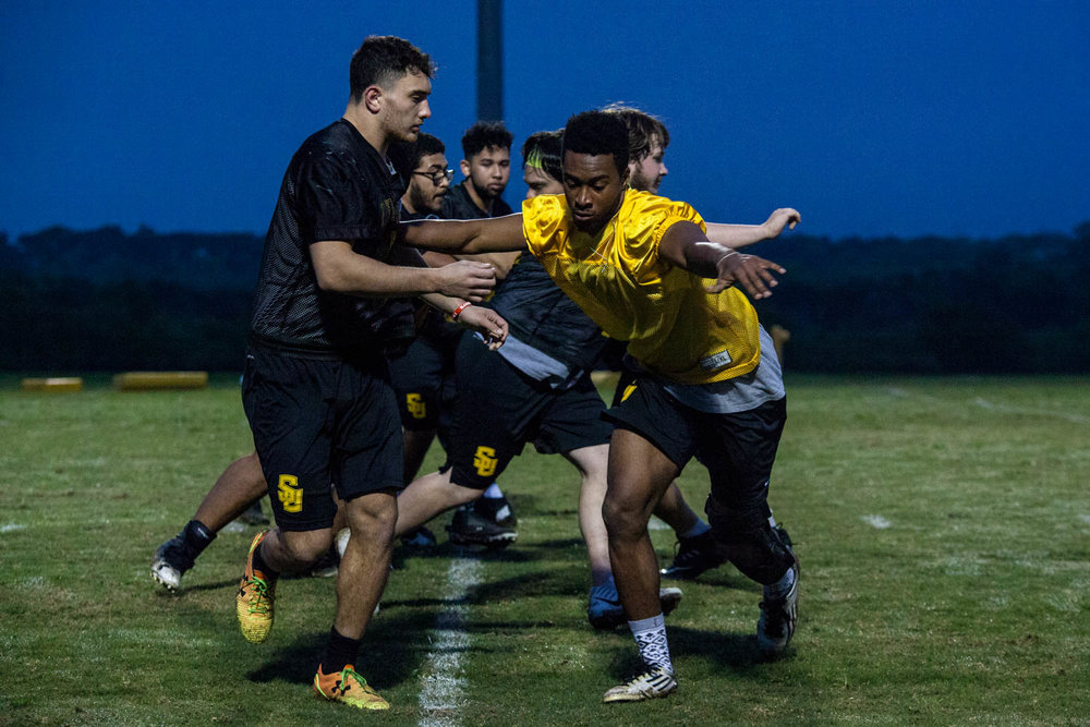 Yusuf Sham, left, and Keyshaan Castle, right, run a defensive line drill at daybreak in April. Southwestern University Pirates put in 16 to 20 hours of work a week during the spring training.