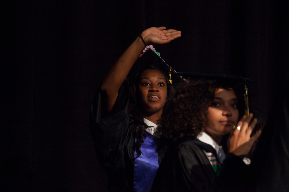 Brianna Nunn, left, and Meranda Nunnery, right, find their friends and family in the crowd before walking the stage at the Southwestern University graduation ceremony Saturday.