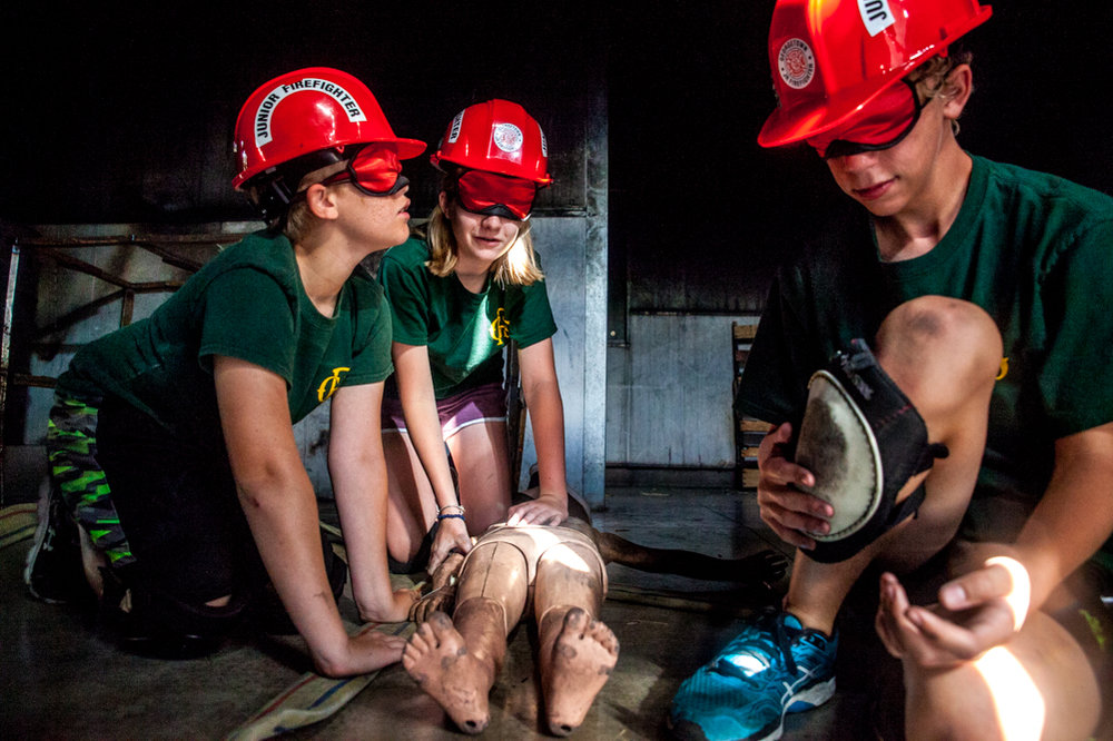 """From left to right William Brousseau, 12, Emma Hilton, 14, and Cole Bishop, 12, try to navigate out of a room with their """"rescue,"""" the mannequin, while blindfolded."""