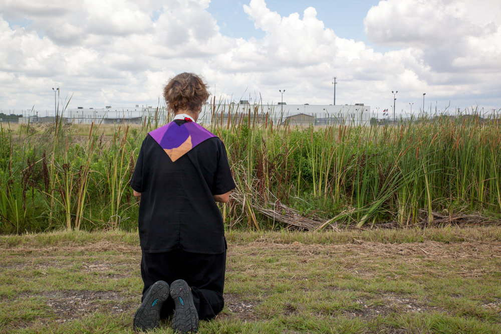 Diana Wilcox, of Newark, took a moment to pray before the T. Don Hutto Residential Center after a prayer service in Taylor on Sunday morning. The service was coordinated with the Episcopal Church's General Convention at the Austin Convention Center.